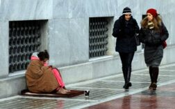 epa03527763 A barefoot homeless woman covered in blankets hopes for donations from pedestrians in a street of central Athens, Greece, 08 January 2013. The number of homeless on the streets of Athens is about 15,000 according to non government organizations, due to economic crisis and deep recession, while temperatures in the Greek capital plunge as result of a cold front that has hit the country.  EPA/ORESTIS PANAGIOTOU