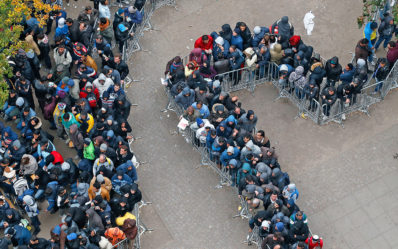 Migrants queue in the compound outside the Berlin Office of Health and Social Affairs (LAGESO) as they wait to register in Berlin, Germany, October 7, 2015. German authorities are struggling to cope with the roughly 10,000 refugees arriving every day, many fleeing conflict in the Middle East. The government expects 800,000 or more people to arrive this year and media say it could be up to 1.5 million.  REUTERS/Fabrizio Bensch TPX IMAGES OF THE DAY   - RTS3DBH