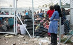 A mother with her child waits outside Moria camp, Lesvos. action aid