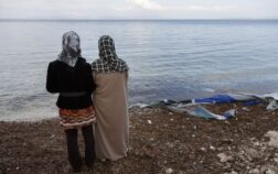 Syrian mother and daughter Fatima and Maisa stand on the shores of Lesvos next to the remains of a boat.